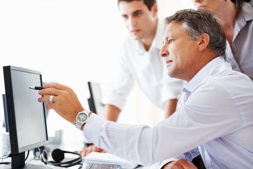 Man Showing Employees Something on Computer